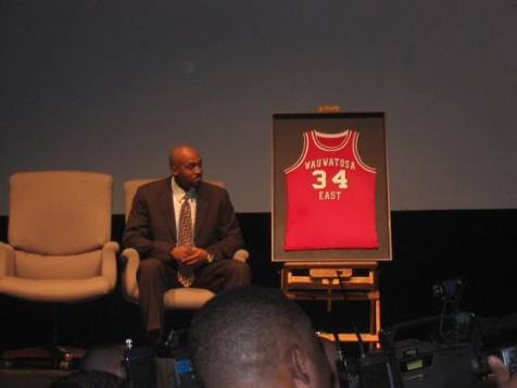 Tony Smith sits on the stage as his newly retired Wauwatosa East jersey is exhibited. That same night, Devin Harris was honored as his jersey was also retired.